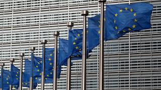 EU flags flutter in front of the European Commission headquarters in Brussels
