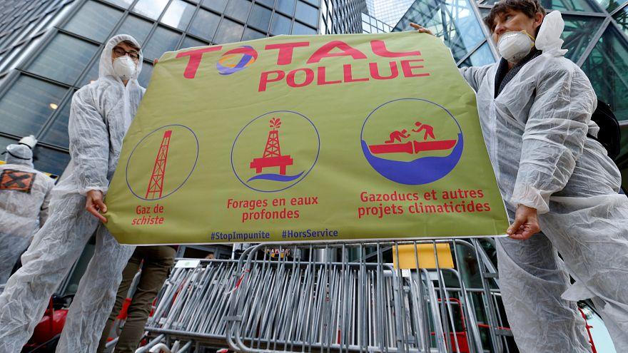El movimiento antiglobalización Attac sostiene una pancarta frente al edificio Total mientras protestan en La Defense, cerca de París, Francia, el 12 de octubre de 2019.