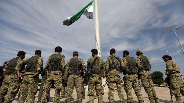 Milícias sírias apoiadas pela Turquia içam bandeira na sidade de Tel Abyad