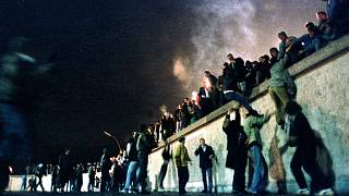 People climb the Berlin Wall at the Brandenburg Gate after the opening of the East German border November 9, 1989.