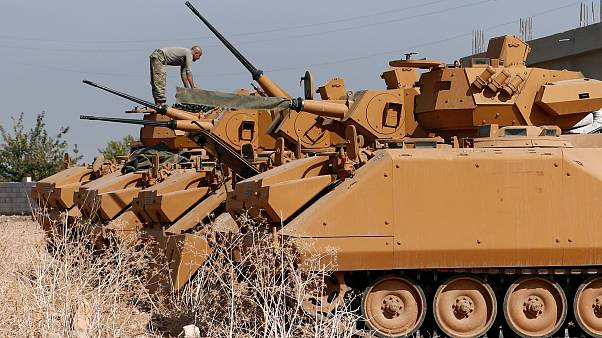 A Turkish soldier stands on top of an armoured personnel carrier near the Turkish-Syrian border in Sanliurfa province