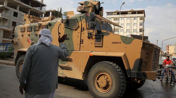 رجل يلوح لمدرعة تابعة للجيش التركي في أقجة قلعة