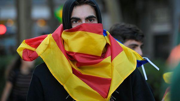 """متظاهر في برشلونة يغطي وجهه بعلم مؤيدي الاستقلال """"إستلادا"""" خلال احتجاجات شهدتها مدينة برشلونة. 16/أكتوبر/2019"""