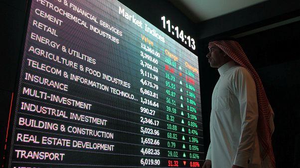 مستثمر سعودي ينظر إلى أسعار الأسهم في سوق المال السعودي تداول.