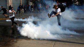 محتج يقذف بقنلة غاز بعيدا وسط شارع في العاصمة سانتياغو، 2019/10/18.