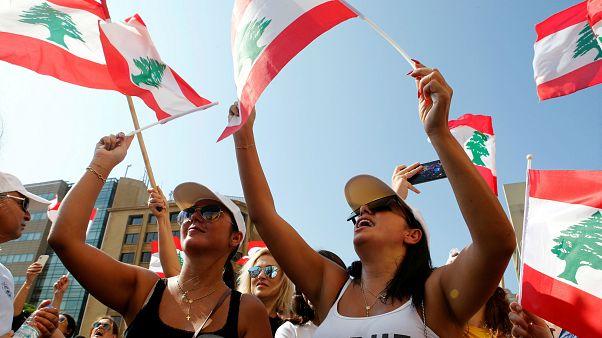 متظاهرتان لبنانيتان ترفعان العلم اللبناني في احتجاجت اليوم الثالث من الحراك الشعبي. 19/10/2019