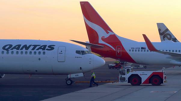 FILE PHOTO: Workers are seen near Qantas Airways, Australia's national carrier, Boeing 737-800 aircraft on the tarmac at Adelaide Airport