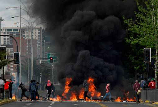 Demonstrators stand next to a burning barricade in Concepcion, Chile October 20, 2019
