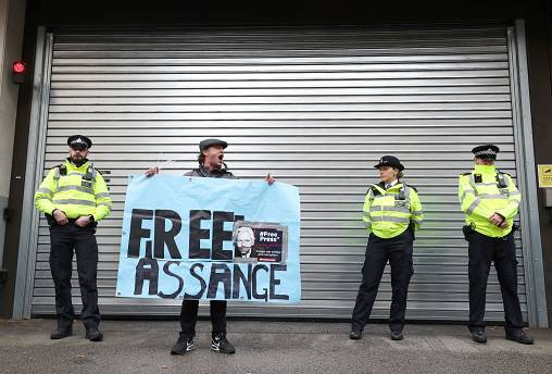 A demonstrator holds a banner during a protest outside a London court, Britain, October 21, 2019.