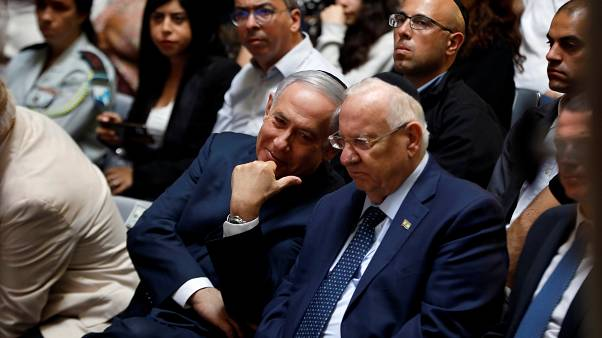 Israeli Prime Minister Benjamin Netanyahu chats with Israeli President Reuven Rivlin during a memorial ceremony for Israeli soldiers killed in the 1973 Middle East War