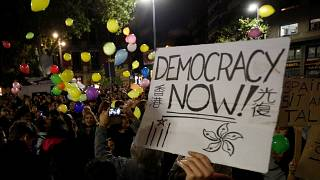 A person holds a placard as pro-independence activists throw balloons during a protest outside the Spanish government delegation offices in Barcelona, Spain October 21, 2019.