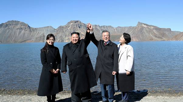 الرئيس الكوري الجنوبي مون جاي إن والزعيم الكوري الشمالي كيم جونغ أون رفقة زوجتيهما، يلتقطان صوراً بجانب بحيرة هيفن ماونت في كوريا الشمالية