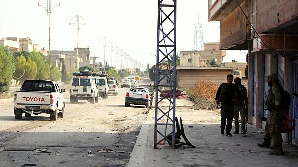 نیروهای تحت حمایت ترکیه در حال تماشای خروج آمبولانسها و خودروهای حامل رزمندههای کرد هستند