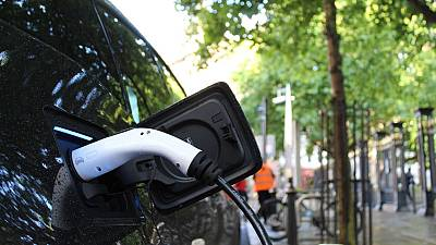 An electric car charges at a roadside charging point
