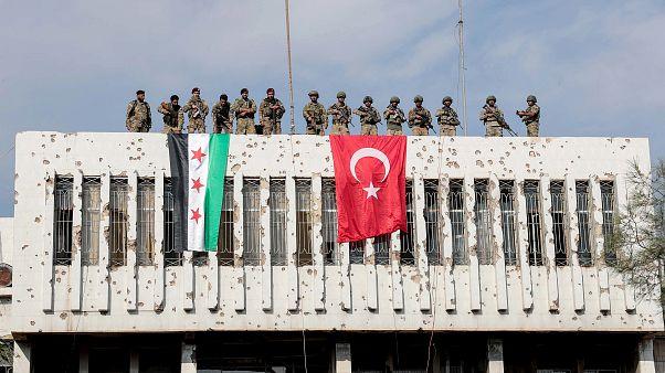 Türkiye sınırına yakın Suriye'nin Rasulayn şehrinde bir binanın üzerine Türk askerleri ve Suriye Milli Ordusu bayrak astı