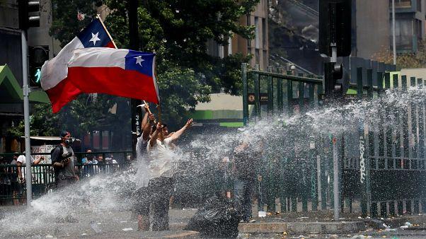 المتظاهرون يلوحون بالأعلام التشيلية بينما تقوم قوات الأمن برشهم بخراطيم المياه أثناء الاحتجاج على النموذج الاقتصادي للدولة في تشيلي في سانتياغو، 23 أكتوبر / تشرين الأول 2019