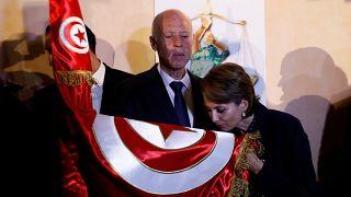 قيس سعيد وزوجته أثناء تقبيلها للعلم التونسي