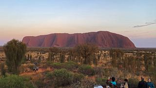 Toursiten vor Australiens berühmtesten Berg: dem Uluru