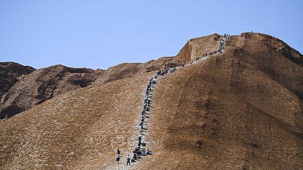 سياح يتسلقون صخرة أولورو في المحمية الأسترالية – 2019/10/25