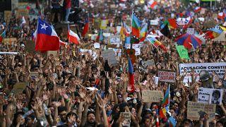 Manifestantes marchan con banderas y carteles durante una protesta contra el Gobierno de Sebastián Piñera en Santiago de Chile, Chile, el 25 de octubre de 2019.