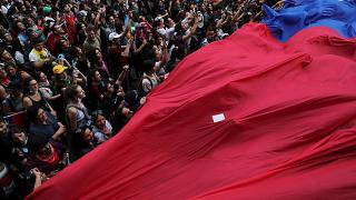 Demonstrators march with a giant flag during a protest against Chile's state economic model in Santiago, Chile October 25, 2019.