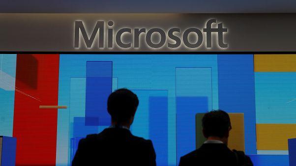 زائران يقفان أمام شاشة عرض في متجر أكسفورد سيركس الجديد من مايكروسوفت قبل افتتاحه في لندن، بريطانيا في 9 يوليو/ تموز 2019.