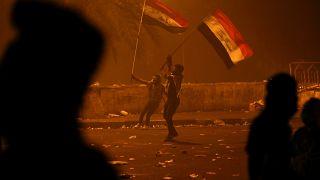متظاهران يرفعان علم العراق خلال احتجاجات وسط بغداد - 2019/10/26