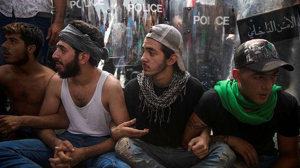 محتجون يجلسون أمام طوق امني وسط بيروت، إثر محاولة الشرطة فتح طريق قطعها المتظاهرون - 2019/10/25