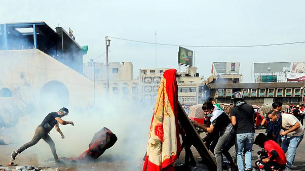 Protesters in Baghdad attempt to throw tear gas canisters back at security services