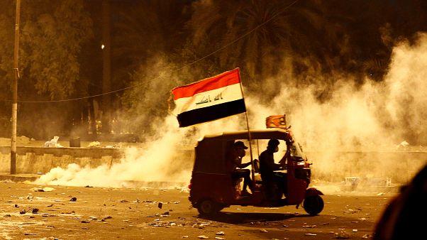 Bağdat'ta göstericiler güvenlik güçlerinin kullandığı biber gazından bir araç ile kaçmaya çalışırken