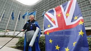 A woman holds a flag during a protest against Brexit outside the EU Commission headquarters in Brussels, Belgium October 9, 2019.