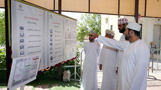 ناخبون بمدينة السمايل شمالي شرقي سلطنة عمان ينظرون إلى قوائم المرشحين لانتخابات مجلس الشورى. 27/10/2019