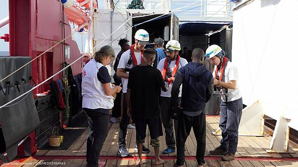 FILE PHOTO: Members of Doctors Without Borders (MSF) talk to migrants onboard Ocean Viking after a rescue operation, October 13, 2019.