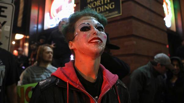 """A counter protester wears a """"Joker"""" mask after a rally by U.S. President Donald Trump in Minneapolis"""