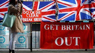 Una mujer toma fotos al lado de las pancartas pro-Brexit frente a las Cámaras del Parlamento en Londres, Reino Unido, el 28 de octubre de 2019.