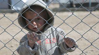 طفل ينظر من وراء سياج في مخيم للنازحين.