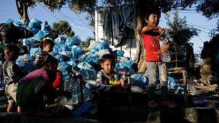 أطفال يملئون الزجاجات بالمياه بجوار مخيم موريا في جزيرة ليسبوس اليونان- أرشيف رويترز