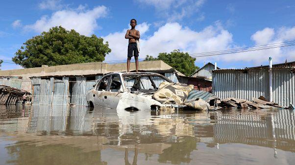 فتى صومالي يقف على أعلى هيكل سيارة بعد أن غمرت مياه الفيضانات ضاحيته في مقديشو. 21/10/2019