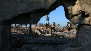 Palestinians inspect a site belonging to Hamas after it was targeted by Israeli warplanes
