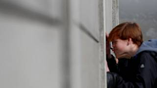 Visitors peers through segments of Wall at the Berlin Wall memorial on Bernauer Strasse in Berlin