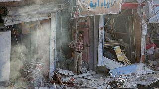 مواطن سوري ينظر إلى السيارة المففخة التي انفجرت في سوق مدينة تل أبيض شمال سوريا. السبت 02/11/2019