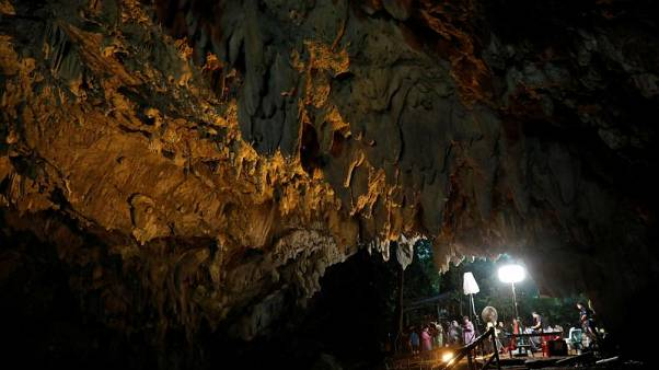 Journalists work in Tham Luang caves during a search for 12 members of an under-16 soccer team and their coach, in the northern province of Chiang Rai