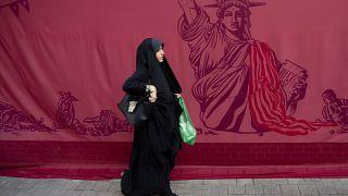 Tahran'da eski ABD Büyükelçiliği binası önünden geçen bir kadın