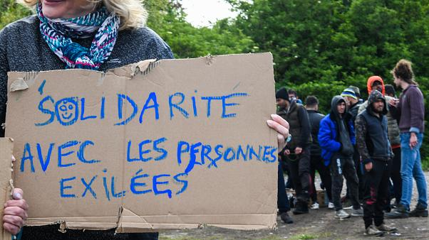 "A woman holds a sign reading ""Solidarity with people in exile"" as she takes part in a solidarity march in support of migrants, in Calais, northern France on May 8, 2019."