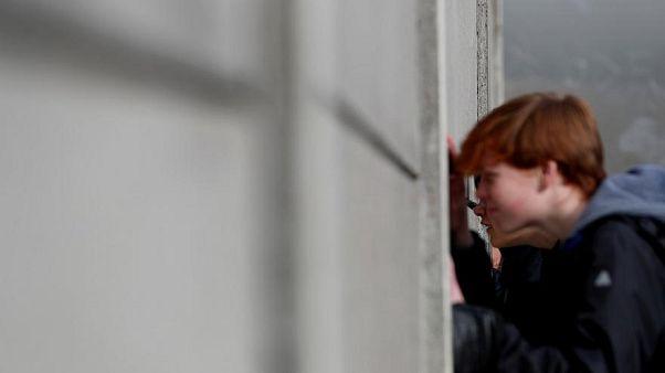 Besucher spicken durch die Mauer an der Gedenkstätte Berliner Mauer, Benauer Straße