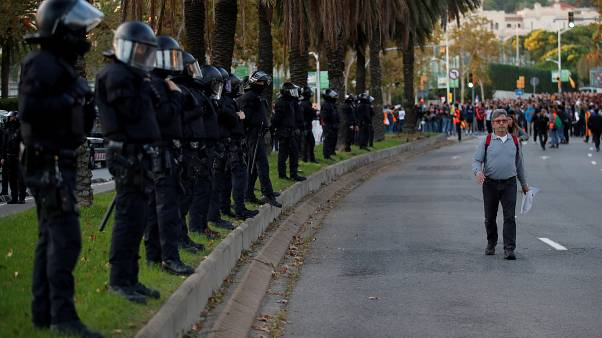 Riot police officers line up as Catalan separatist protesters gather outside the Palau de Congressos de Catalunya