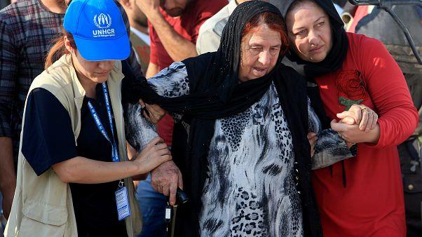 عاملة ضمن فريق إغاثة تابع للامم المتحدة تساعد إحدى النازحات قرب مخيم دهوك - 2019/10/18 -