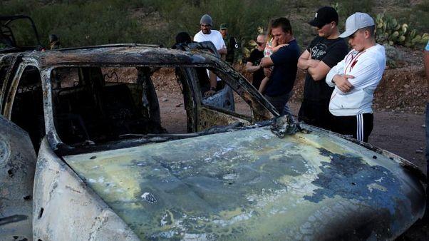 Parenti delle vittime osservano sgomenti uno delle auto carbonizzate.