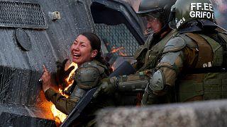 Una mujer policía en llamas durante los disturbios del lunes en Santiago