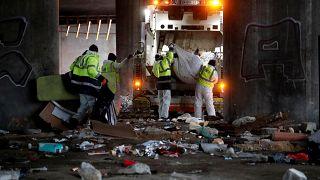 Workers clean the site after a migrant makeshift camp was evacuated under the Porte de la Villette ring bridge in Paris, France.